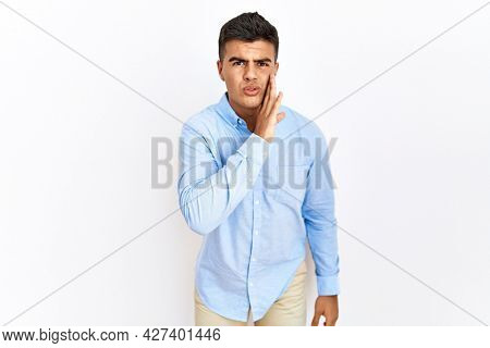 Young hispanic man wearing business shirt standing over isolated background hand on mouth telling secret rumor, whispering malicious talk conversation