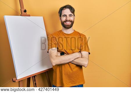 Caucasian man with beard standing by painter easel stand happy face smiling with crossed arms looking at the camera. positive person.
