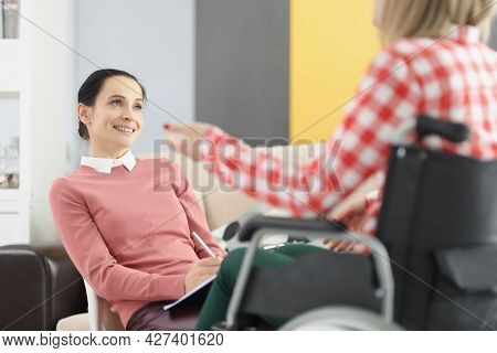 Woman Psychologist Consults Disabled Woman In Chair