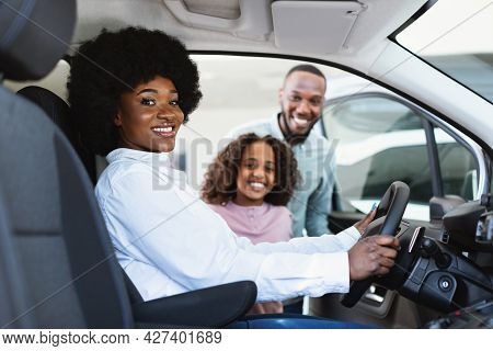 Test Drive. Black Woman Sitting In Driver Seat Of New Car, Choosing Vehicle With Husband And Daughte