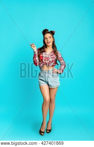 Full Length Portrait Of Playful Happy Pinup Woman In Retro Style Wear Posing Over Blue Studio Backgr