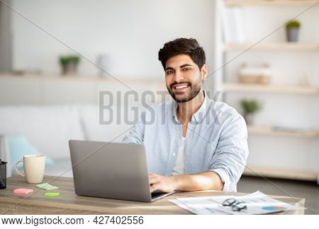 Millennial Freelancer. Portrait Of Happy Arab Man Sitting At Desk With Laptop, Working At Home Offic