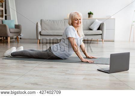 Mature Woman Stretching Back On Mat, Cobra Pose