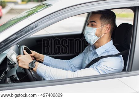 Middle-eastern Businessman In Face Mask Driving Car, Side View
