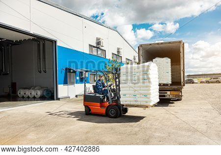 A Man On A Forklift Works In A Large Warehouse, Unloads Bags Of Raw Materials Into A Truck For Trans