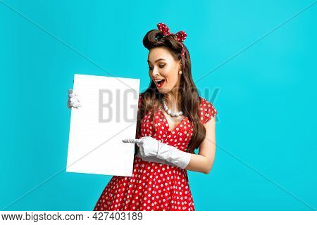 Excited Pinup Retro Style Woman Pointing At Empty Advertising Banner With Copy Space On Blue Studio