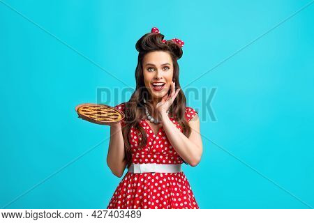 Excited Pinup Retro Style Housewife Holding Homemade Pie, Feeling Excited On Blue Studio Background
