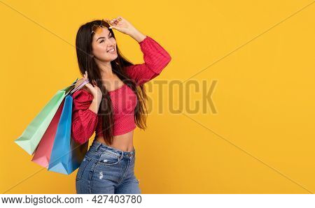 Summer Shopping Concept. Dreamy Armenian Woman With Colorful Bags, Looking At Empty Space On Yellow