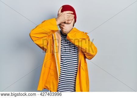 Caucasian man with beard wearing yellow raincoat covering eyes and mouth with hands, surprised and shocked. hiding emotion