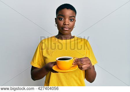 Young african american woman holding coffee relaxed with serious expression on face. simple and natural looking at the camera.