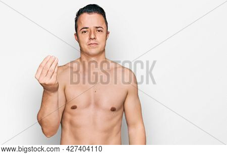 Handsome young man wearing swimwear shirtless doing italian gesture with hand and fingers confident expression