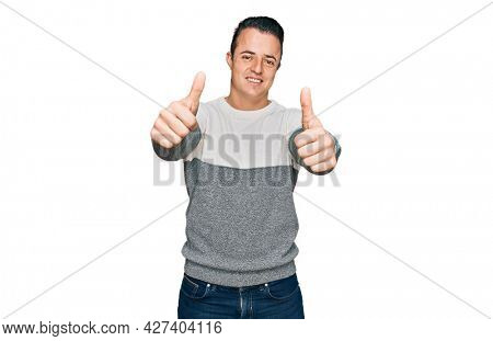 Handsome young man wearing casual winter sweater approving doing positive gesture with hand, thumbs up smiling and happy for success. winner gesture.