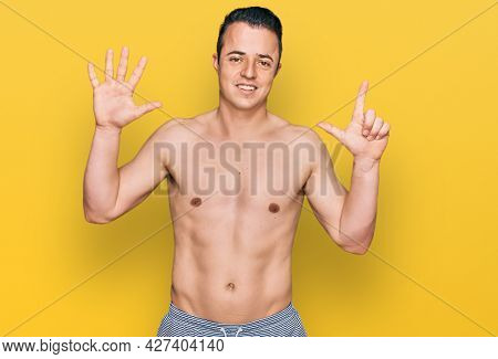 Handsome young man wearing swimwear shirtless showing and pointing up with fingers number seven while smiling confident and happy.