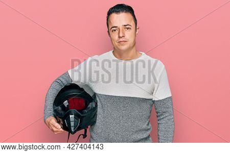 Handsome young man holding motorcycle helmet thinking attitude and sober expression looking self confident