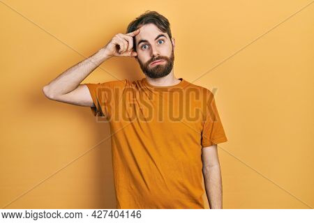 Caucasian man with beard wearing casual yellow t shirt worried and stressed about a problem with hand on forehead, nervous and anxious for crisis