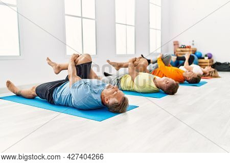Group of middle age people concentrate  training yoga at sport center.