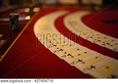 View On Poker Table With Cards And Chips In Low Ligh