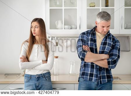 Offended Mature Married Couple Standing In Kitchen With Crossed Arms After Quarrel At Home