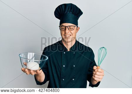 Handsome young man holding bread dough and blender winking looking at the camera with sexy expression, cheerful and happy face.