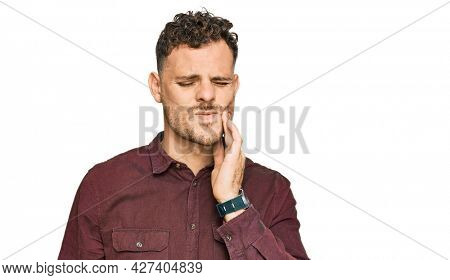 Young hispanic man wearing casual clothes touching mouth with hand with painful expression because of toothache or dental illness on teeth. dentist