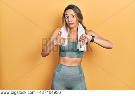 Beautiful hispanic woman wearing sportswear and towel doing thumbs up and down, disagreement and agreement expression. crazy conflict