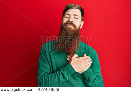 Redhead man with long beard wearing casual clothes smiling with hands on chest, eyes closed with grateful gesture on face. health concept.