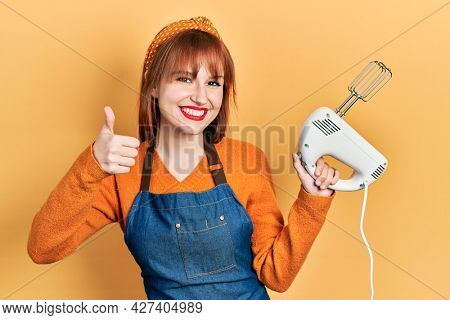 Redhead young woman holding pastry blender electric mixer smiling happy and positive, thumb up doing excellent and approval sign