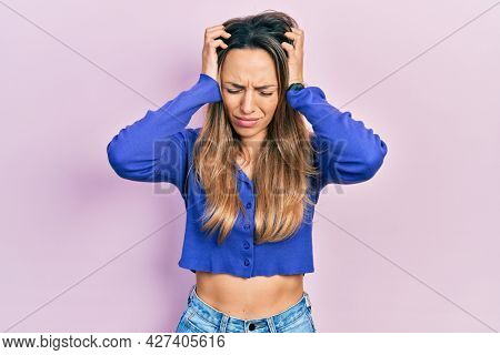 Beautiful hispanic woman wearing casual blue shirt suffering from headache desperate and stressed because pain and migraine. hands on head.