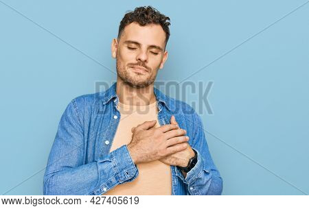 Young hispanic man wearing casual clothes smiling with hands on chest with closed eyes and grateful gesture on face. health concept.