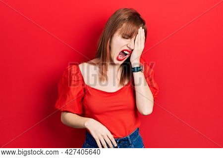 Redhead young woman wearing casual red t shirt yawning tired covering half face, eye and mouth with hand. face hurts in pain.