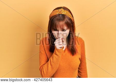 Redhead young woman wearing casual orange sweater feeling unwell and coughing as symptom for cold or bronchitis. health care concept.