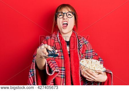 Redhead young woman eating popcorn using tv control angry and mad screaming frustrated and furious, shouting with anger looking up.