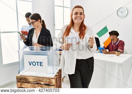 Young irish voter woman smiling happy holding ireland flag at vote center.