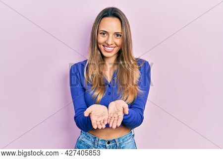 Beautiful hispanic woman wearing casual blue shirt smiling with hands palms together receiving or giving gesture. hold and protection