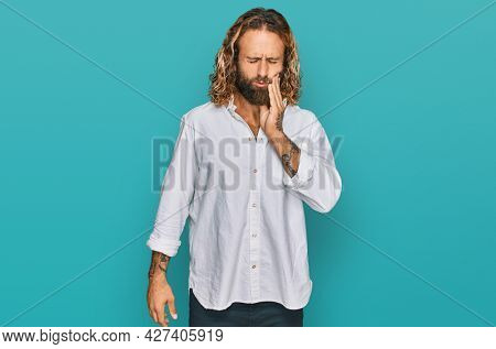 Handsome man with beard and long hair wearing casual clothes touching mouth with hand with painful expression because of toothache or dental illness on teeth. dentist