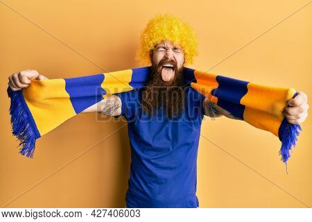 Redhead man with long beard football hooligan cheering game wearing funny wig sticking tongue out happy with funny expression.