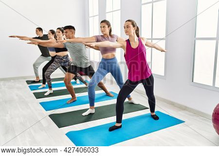 Group of young people concentrated training yoga at sport center.