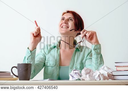 Young Red-haired Woman At A Desk With A Pencil In Her Hands Looks Up With Inspiration. Woman Writer