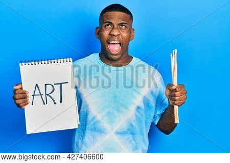 Young black man holding art notebook and painter brushes angry and mad screaming frustrated and furious, shouting with anger looking up.