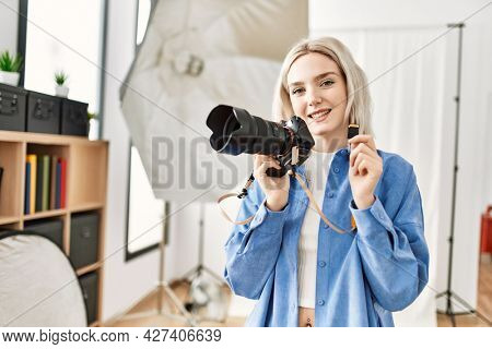 Beautiful blonde woman working as professional photographer at photography studio. Standing holding sdxc storage memory card