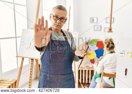 Middle age caucasian man drawing canvas at art studio with open hand doing stop sign with serious and confident expression, defense gesture