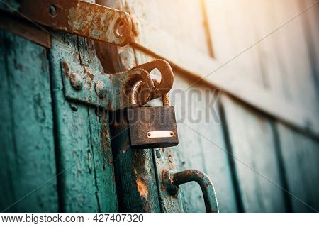 An Old Rusty Lock Hangs On The Abandoned Wooden Gate, Painted Blue, Which Closes Them And Is Illumin
