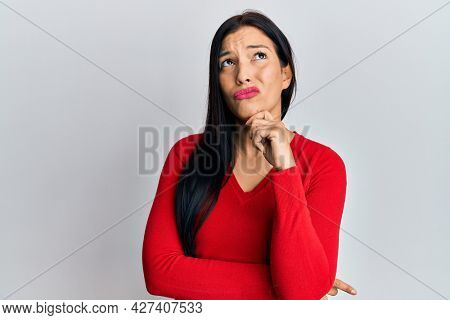 Young latin woman wearing casual clothes thinking concentrated about doubt with finger on chin and looking up wondering