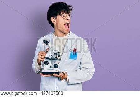 Handsome hipster young man wearing lab coat holding microscope angry and mad screaming frustrated and furious, shouting with anger. rage and aggressive concept.
