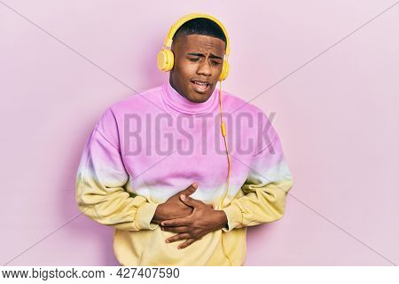 Young black man listening to music wearing headphones with hand on stomach because nausea, painful disease feeling unwell. ache concept.
