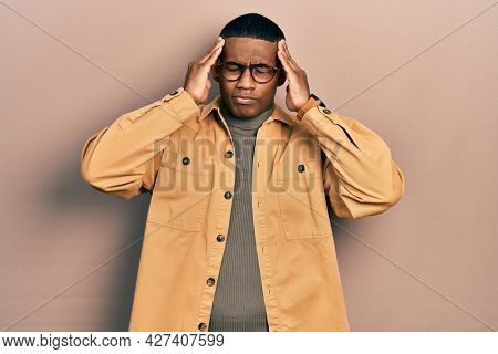 Young black man wearing casual clothes and glasses suffering from headache desperate and stressed because pain and migraine. hands on head.