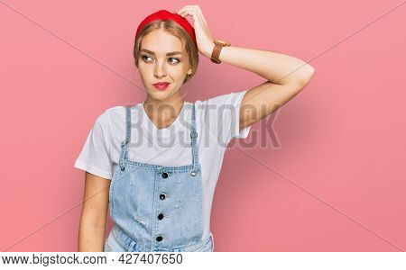 Young caucasian girl wearing casual clothes confuse and wondering about question. uncertain with doubt, thinking with hand on head. pensive concept.