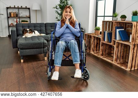 Young beautiful woman sitting on wheelchair at home praying with hands together asking for forgiveness smiling confident.