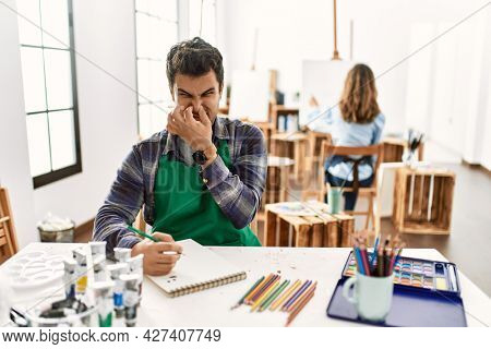 Young artist man at art studio smelling something stinky and disgusting, intolerable smell, holding breath with fingers on nose. bad smell