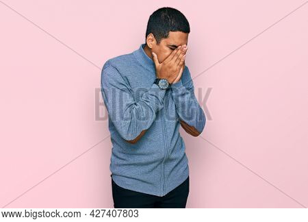 Young handsome hispanic man wearing casual sweatshirt with sad expression covering face with hands while crying. depression concept.